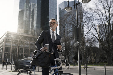 Grey-haired businessman with bicycle and coffee to go in the city - SBOF00785