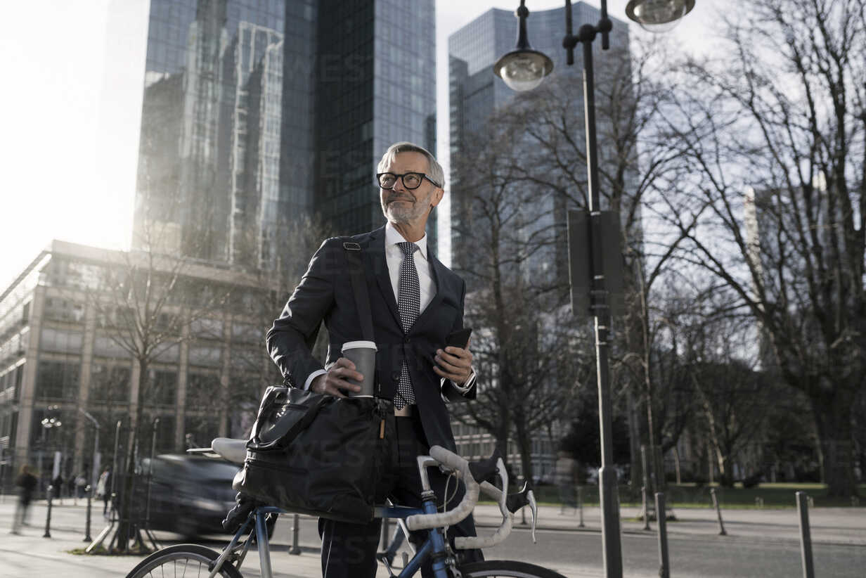 Grey-haired businessman with bicycle and coffee to go in the city - SBOF00785 - Steve Brookland/Westend61