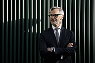 Portrait of grey-haired businessman in front of green wall - SBOF00788