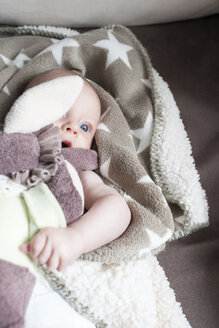 Portrait of baby girl wrapped in blanket lying on a couch - CSTF01403