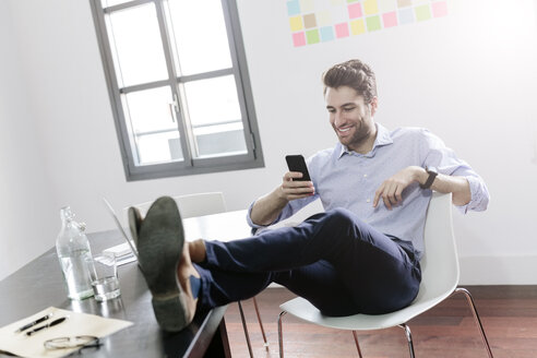 Young businessman working in office, using smartphone - GIOF03259