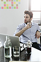 Young businessman sitting at desk with pot of coffee - GIOF03262