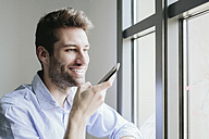 Young businessman working in office, using smartphone - GIOF03277