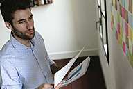 Young businessman working in office, holding documents - GIOF03280