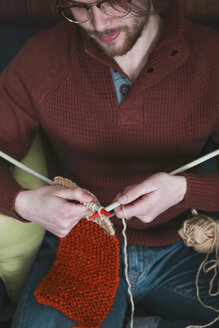 Young man knitting a scarf, partial view - RTBF01005