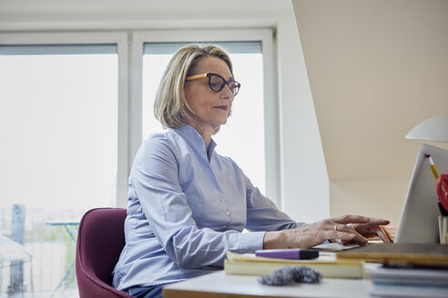 Mature woman at home using laptop at desk - RBF06029