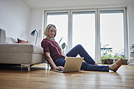 Mature woman at home using laptop on the floor - RBF06035