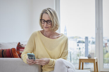 Mature woman at home looking at cell phone on the sofa - RBF06038