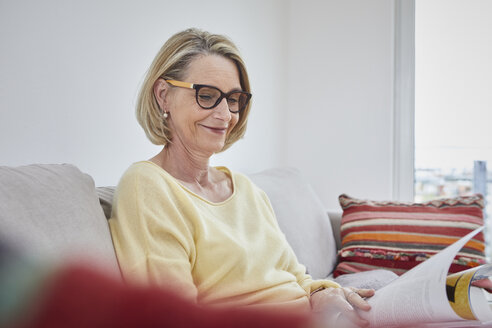 Smiling mature woman at home on the sofa reading a magazine - RBF06041