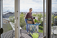 Smiling mature woman caring for plants on balcony - RBF06050