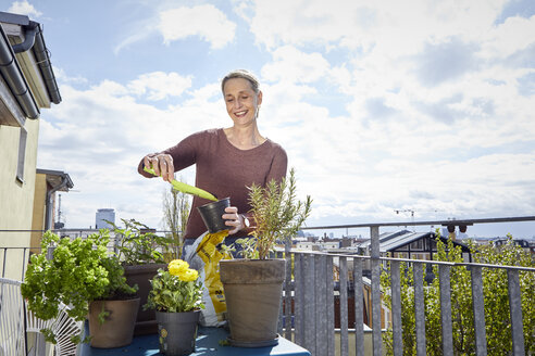 Smiling mature woman caring for plants on balcony - RBF06053