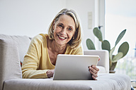 Smiling mature woman at home using tablet on the sofa - RBF06059