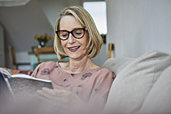Smiling mature woman at home on the sofa reading a book - RBF06062