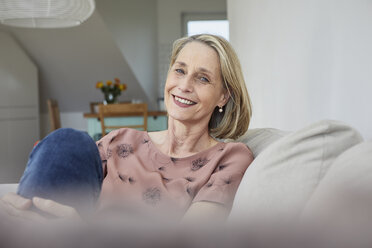 Portrait of smiling mature woman at home on the sofa - RBF06065