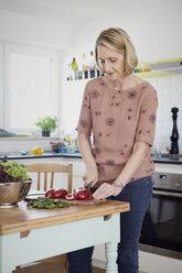 Mature woman preparing a salad in kitchen - RBF06071