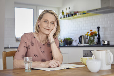 Portrait of mature woman with notebook at kitchen table - RBF06074