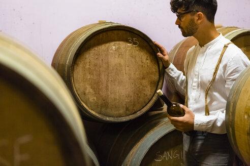 Man looking at wine barrel in wine cellar - MGIF00134