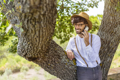 Smiling man wearing old-fashioned clothes talking on cell phone - MGIF00137