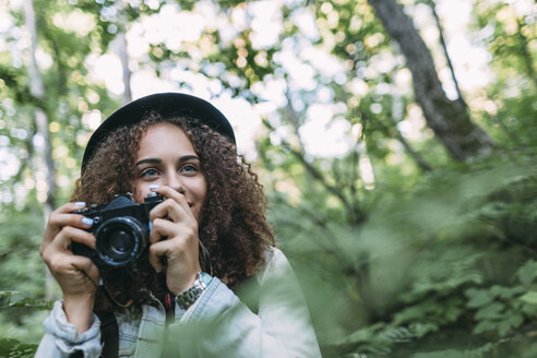 Portrait of smiling teenage girl taking pictures in nature - VPIF00095