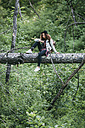 Teenage girl with camera sitting on deadwood in nature - VPIF00098