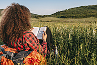 Back view of teenage girl reading book on a meadow - VPIF00110