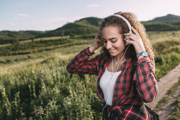 Teenage girl listening music with headphones in nature - VPIF00113