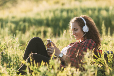 Teenage girl listening music with headphones on a meadow looking at cell phone - VPIF00116