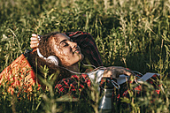 Teenage girl with backpack lying on a meadow listening music with headphones and cell phone - VPIF00122