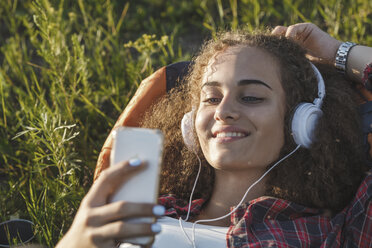 Teenage girl with backpack lying on a meadow listening music with headphones and cell phone - VPIF00125