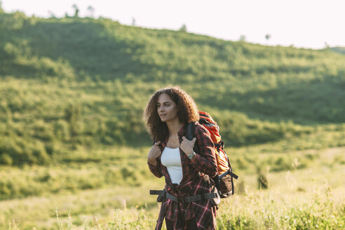 Teenage girl with backpack hiking in nature - VPIF00128