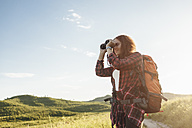 Teenage girl with backpack using binoculars in nature - VPIF00131