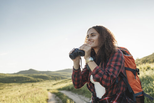 Teenage girl with backpack and binoculars in nature - VPIF00134
