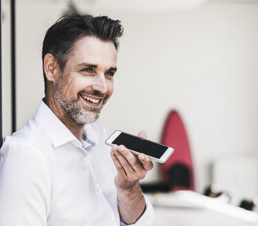 Happy businessman using cell phone in office - UUF11682