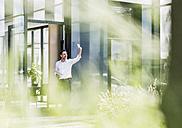 Businessman outside office building taking a selfie - UUF11685