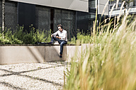 Businessman with headphones sitting on wall outside office building reading document - UUF11688
