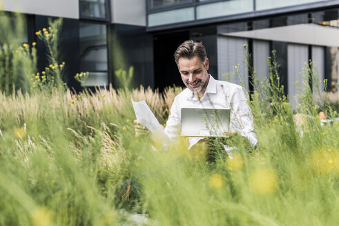 Smiling businessman working in grass outside office building - UUF11691