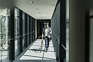 Businessman with cell phone pushing bicycle in office passageway - UUF11697