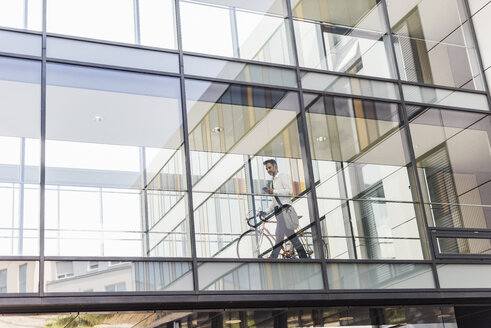 Businessman with cell phone pushing bicycle in office passageway - UUF11700