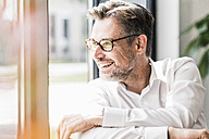 Smiling businessman with glasses looking sideways - UUF11706