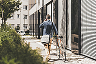 Smiling businessman with cell phone pushing bicycle - UUF11724