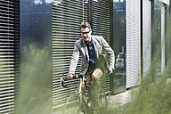 Shocked businessman on bicycle looking at cell phone - UUF11727