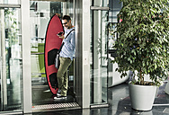 Smiling businessman with surfboard and cell phone in elevator - UUF11733