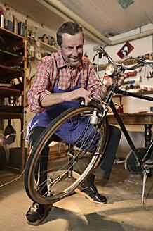 Senior man repairing bicycle in his workshop - ECPF00125