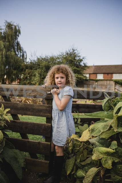 Portrait of little girl opening gate in the garden - NMSF00160
