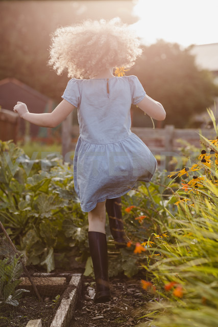 Back view of happy little girl jumping  in the garden - NMSF00163