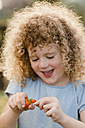 Portrait of laughing little girl with tomato - NMSF00172