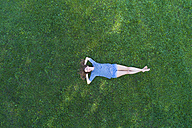 Young woman lying on grass, daydreaming - MAEF12417