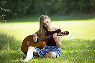Young woman sitting on meadow, playing guitar - MAEF12426