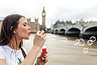 UK, London, woman making soap bubbles near Westminster Bridge - MGOF03628