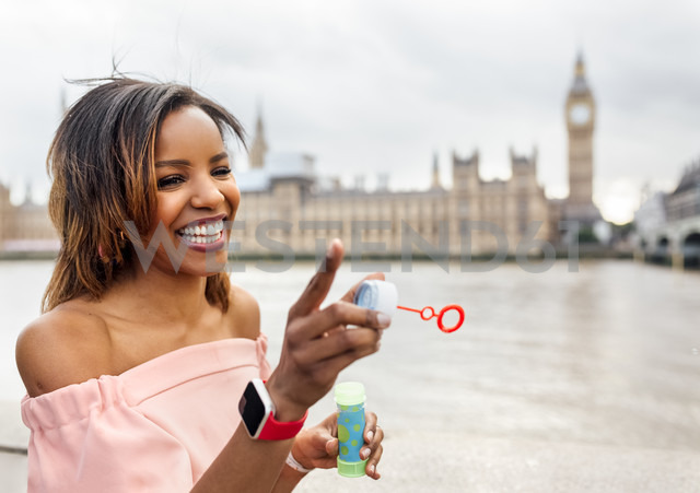 UK, London, happy woman making soap bubbles near Palace of Westminster - MGOF03631 - Marco Govel/Westend61